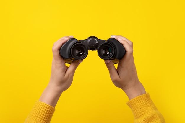 Binocolo in mano su sfondo giallo, trova e cerca il concetto.