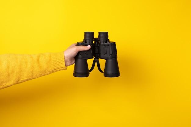 Binocolo in mano su sfondo giallo, concetto di ricerca.
