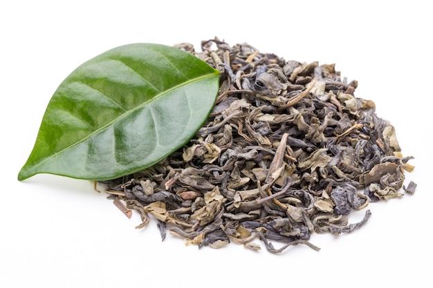Foglia di tè verde bio isolata sulla superficie bianca