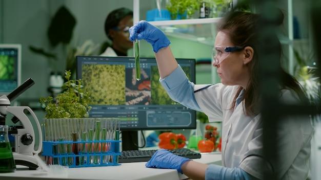 Medico di biochimica che esamina test chimico al microscopio