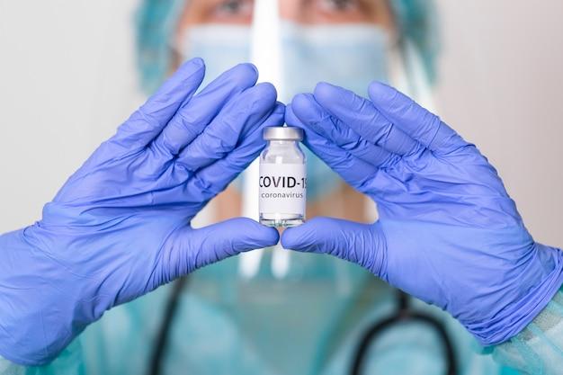 Rischio biologico. epidemia del coronavirus covid-19. il medico in tuta protettiva, maschera e visiera tiene una siringa per iniezione e un vaccino.