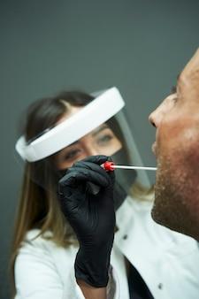 Biologo che conduce un test sul coronavirus. biologo con guanti e maschera protettiva che esegue un test del coronavirus su una persona in una clinica.