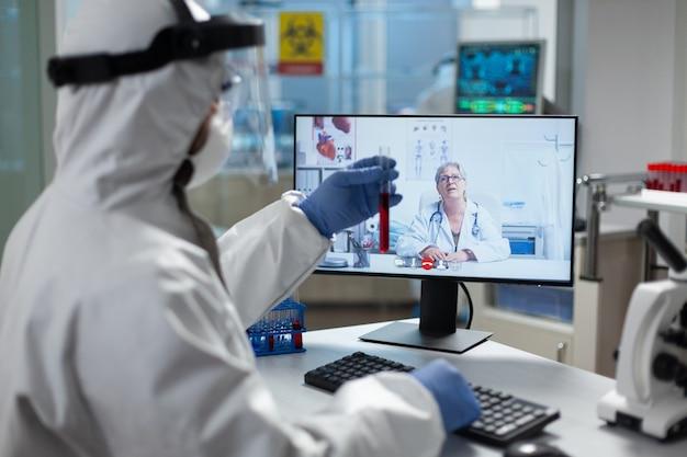 Uomo biologo che tiene in mano una provetta con sangue infetto che discute con il ricercatore