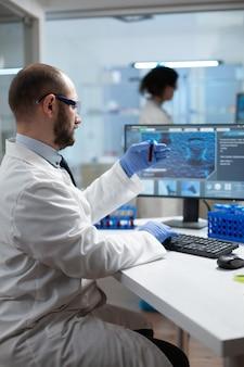 Uomo ricercatore biologo che tiene vacutainer medico con campione di sangue