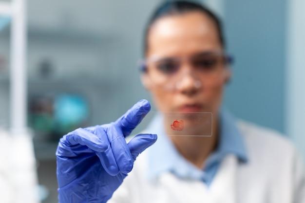 Scienziato biologo che tiene in mano un bicchiere con un campione di sangue che lavora all'esperimento di microbiologia