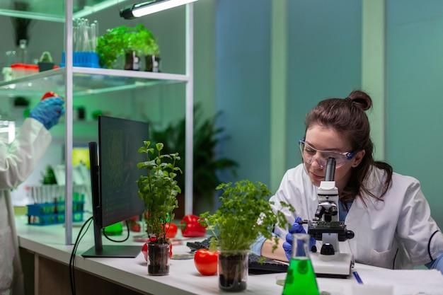 Scienziato biologo che esamina un campione di foglie utilizzando un microscopio medico