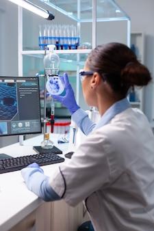 Donna biologa che guarda il virus batterico usando una capsula di petri medica che lavora all'esperienza di infezione genetica...