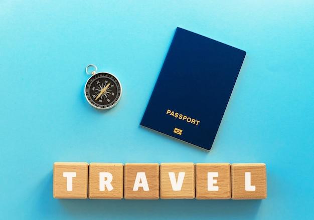 Passaporto biometrico, bussola e cubi di legno con testo viaggio sull'azzurro