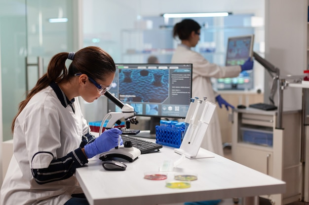Scienziato di biotecnologia che guarda attraverso il microscopio che analizza materiale genetico
