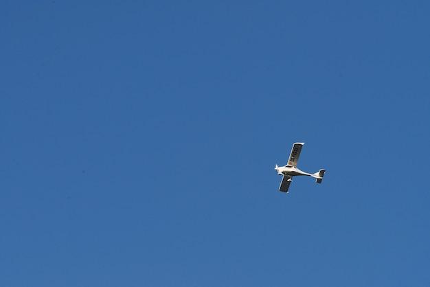 Biplano che vola alto nel cielo blu al giorno pieno di sole.