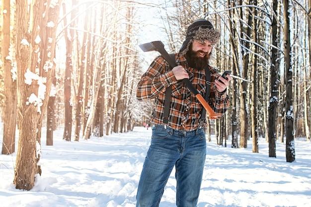 Uomo della foresta invernale di betulla con ascia