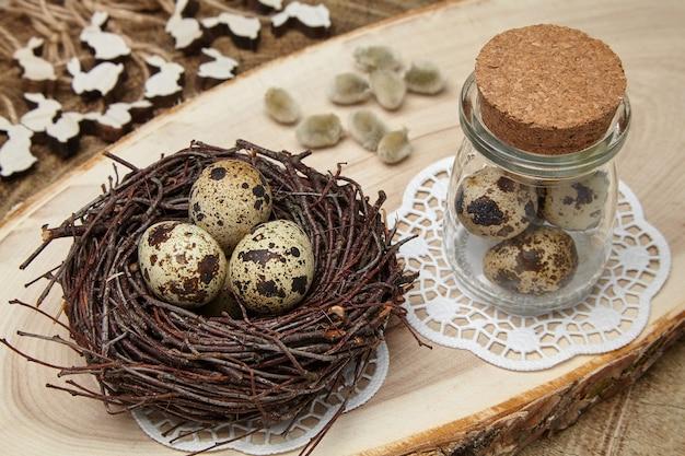 Uova di uccello in un nido, uova in un barattolo, lepri di legno e gemme di salice su una sega di legno. concetto di pasqua