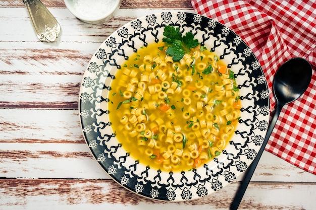 Vista dall'alto di una squisita zuppa di pollo e verdure con piccoli noodles e prezzemolo, fatta in casa. servito su un piatto vintage su un tavolo in legno rustico. concetto di cibo naturale e sano