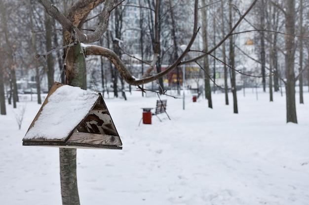 Mangiatoia per uccelli nella neve nel parco invernale