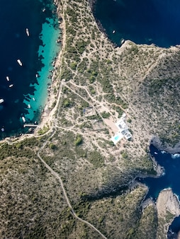 Vista a volo d'uccello isola paradisiaca con acque turchesi.