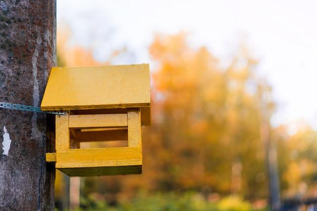 Una casetta per uccelli a forma di casa gialla è appesa a un albero