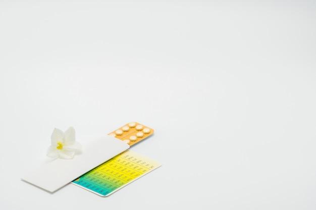 Pillole anticoncezionali o pillola contraccettiva con astuccio di carta e fiore bianco su fondo bianco. concetto di pianificazione familiare. terapia ormonale sostitutiva. trattamento dell'acne ormonale con pillola anti-androgena.