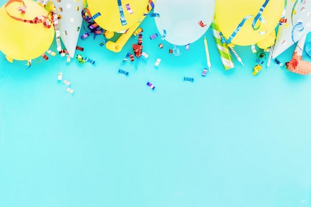 Sfondo di palloncino di compleanno con stelle filanti colorate, coriandoli e cappelli di festa di compleanno sul blu