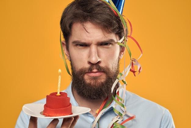 Ragazzo di compleanno in un berretto con una torta di compleanno in mano e una candela