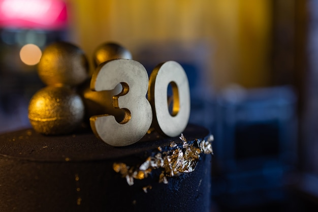 Torta di compleanno numero 30 stelle cielo e luna concetto, la candela blu è fuoco da accendino. copyspace sul lato destro dello schermo. vista ravvicinata.