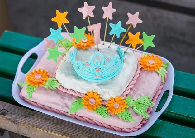 Torta di compleanno con fiori colorati, stelle e diadema