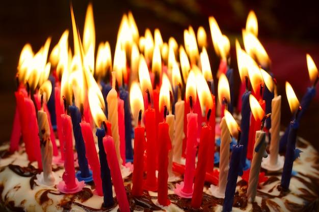 Torta di compleanno con tante candele accese