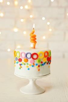 Torta di compleanno con una candela su bianco.