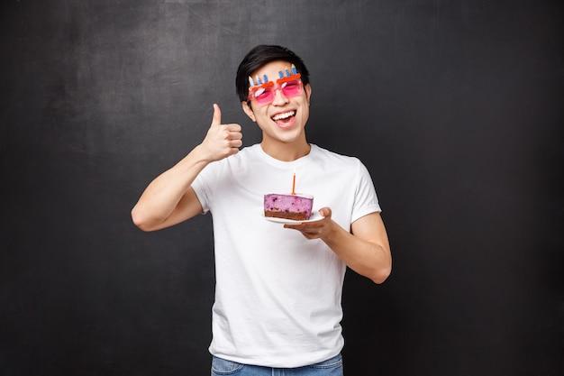 Compleanno, celebrazione e concetto di festa. uomo asiatico divertente emozionante in bicchieri sciocchi godendo b-day tenendo la torta con candela, facendo desiderio ridere e sorridere, mostra pollice in su, muro nero