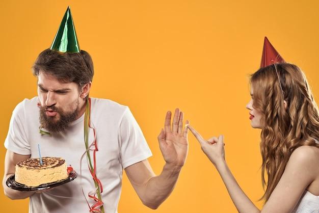 Coppie di compleanno con una torta e una candela indossando cappelli da festa isolati