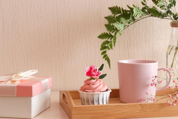Bigné di compleanno e tazza di caffè sul vassoio in legno con confezione regalo sul tavolo