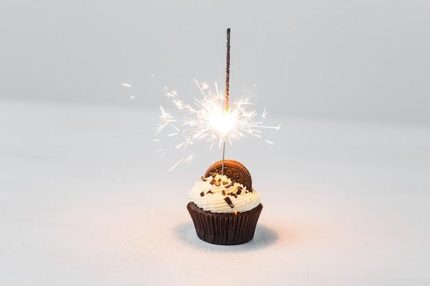 Bigné di compleanno con lo sparkler sopra priorità bassa bianca.