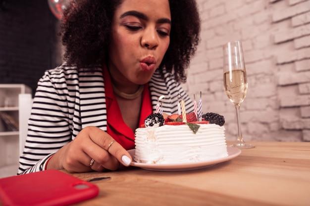 Dessert di compleanno. bella piccola torta in piedi sul tavolo con una bella giovane donna che soffia alle sue candeline