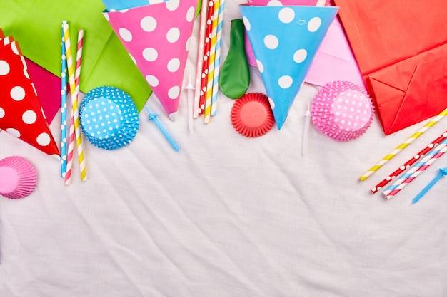Compleanno piatto laico, vista dall'alto e copia spazio per testo, cornice o sfondo con elementi colorati del festival, cappelli da festa e stelle filanti, biglietto di auguri di compleanno o festa.