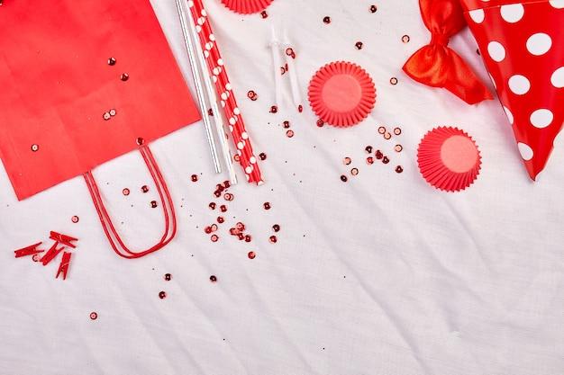 Compleanno piatto laico, vista dall'alto e copia spazio per testo, cornice o sfondo con elementi del festival rosso, cappelli da festa e stelle filanti, biglietto di auguri di compleanno o festa.