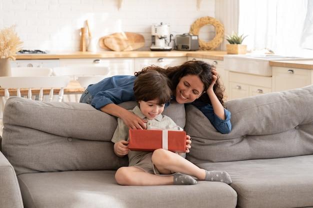 Regalo di compleanno per mamma che si prende cura dei bambini che saluta bambino con scatola regalo per eventi festivi