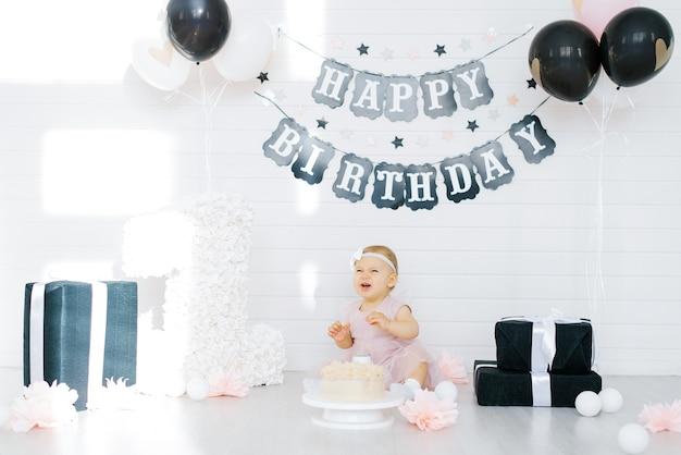 Ragazza di compleanno 1 anno seduta nella zona della foto e piange