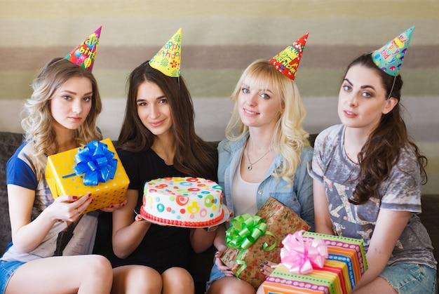 Ragazza di compleanno in posa con regali e torta.