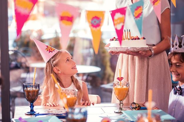 Ragazza di compleanno che indossa il cappello del partito guardando la torta
