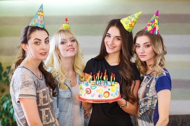 Compleanno. ragazze in posa con la torta per il compleanno.