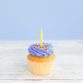 Concetto di auguri di compleanno. candela gialla su un muffin o un cupcake.