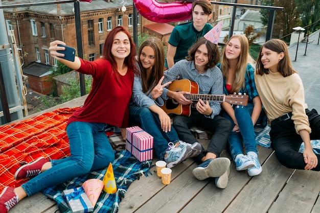 Selfie di gruppo di compleanno su un tetto. amici che scattano foto da condividere sui social network. stile di vita giovanile bff