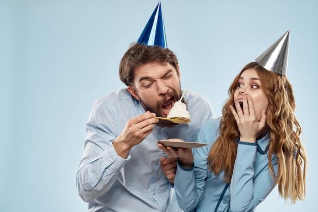 Compleanno uomo e donna con un cupcake e una candela in un cappello da festa