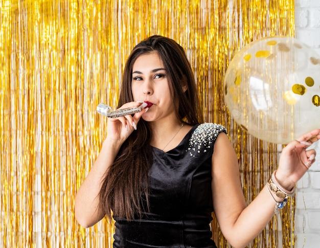 Festa di compleanno. bella donna castana in vestito da partito nero che celebra il suo compleanno che soffia il produttore di rumore