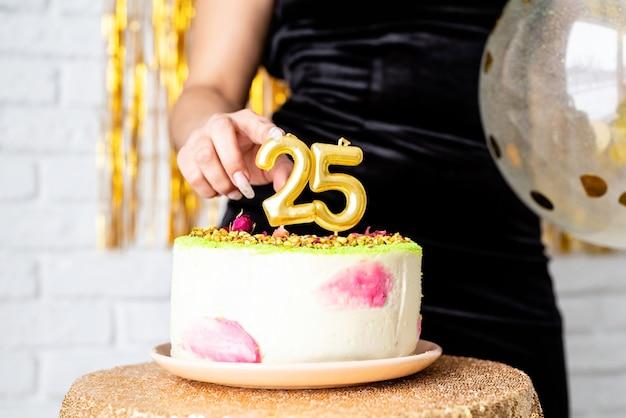 Festa di compleanno. bella donna castana in vestito da partito nero che tiene palloncino che festeggia il suo compleanno tagliando la torta