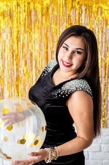 Festa di compleanno. bella donna castana sorridente in vestito da partito nero che celebra il suo pallone della holding di compleanno