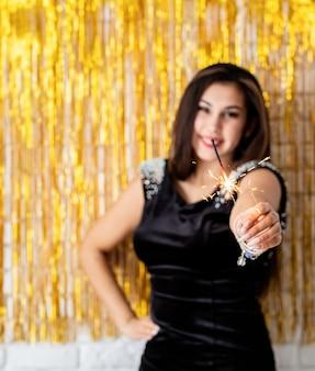 Festa di compleanno. bella giovane donna che tiene sparkler e palloncino su sfondo dorato