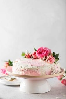 Concetto di festa di compleanno con torta bianca rosa decorata con rose rosa, immagine di messa a fuoco selettiva