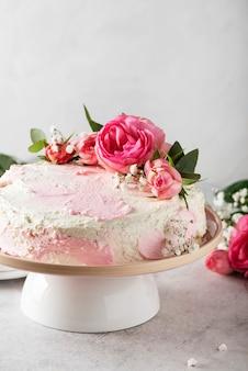 Concetto di festa di compleanno con torta bianca rosa decorata con rose rosa