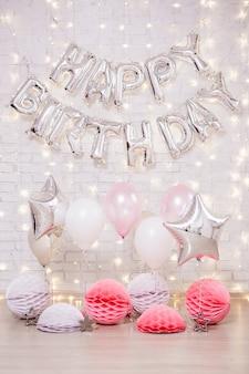 Decorazione della festa di compleanno - lettere di buon compleanno mongolfiere, stelle e palline di carta su un muro di mattoni bianchi con luci