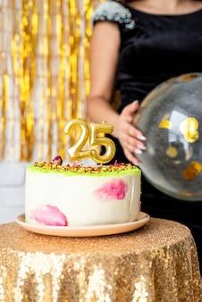 Festa di compleanno. candele dorate 25 sulla torta di compleanno su sfondo glitter dorato